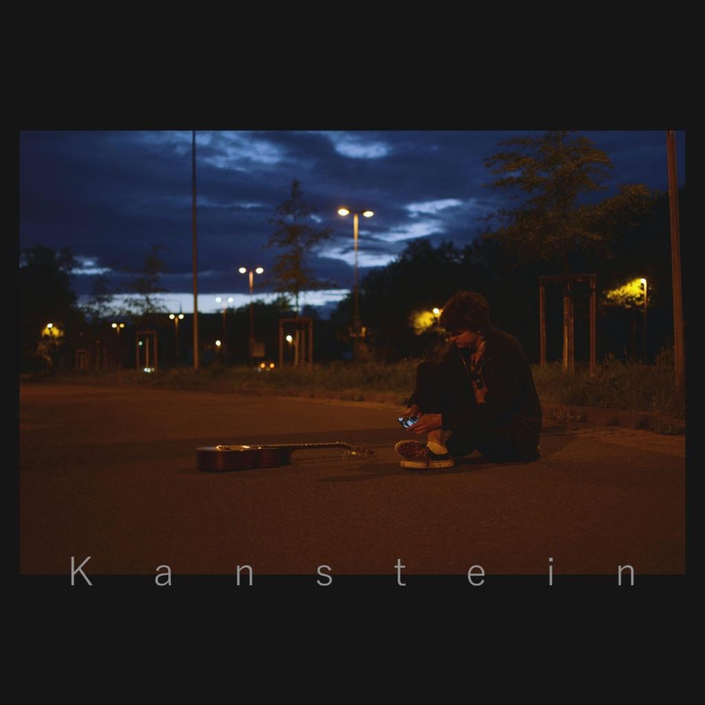 Cover Album Kanstein, beleuchtete Straße bei Nacht, Mann sitzend mit Gitarre daneben liegend